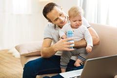 Padre amoroso allegro che dà una bottiglia di acqua al suo bambino gridante Immagini Stock
