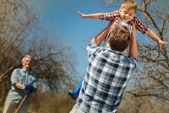 Padre amoroso che tiene suo figlio nell'aria immagini stock libere da diritti