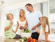 Padre & figlio che preparano insalata in cucina moderna Immagine Stock