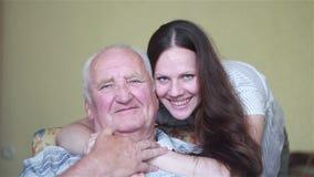 Padre anziano che si siede in una sedia che guarda fuori abbracciare della figlia e della finestra stock footage