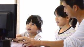 Padre asiático And Cute Daughter que juega el ordenador almacen de metraje de vídeo