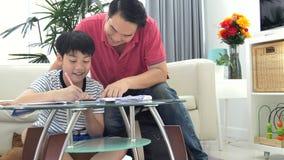 Padre asiático e hijo que hacen la preparación en la tabla en la sala de estar almacen de video