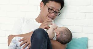 Padre asiático joven que alimenta su fórmula de la leche del bebé de una botella en la sala de estar almacen de metraje de vídeo
