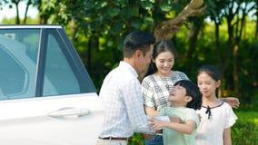 Padre asiático que detiene a su hijo hacia fuera del coche con la madre y la hija por otra parte
