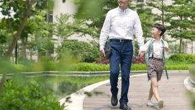 Padre asiático que escolta al hijo que va a la escuela en la cámara lenta del jardín metrajes
