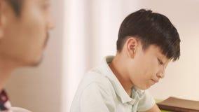 Padre asiático que habla y que aconseja a su adolescente frustrado en Imagen de archivo