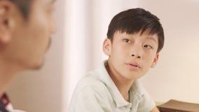 Padre asiático que habla y que aconseja a su adolescente frustrado en Fotos de archivo libres de regalías