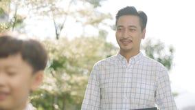 Padre asiático que sonríe y que mira a su hijo en la manera a la escuela por la mañana Fotografía de archivo libre de regalías