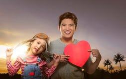 Padre asiatico allegro e figlia con il gioco del cappello dell'aviatore immagine stock