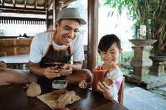 Padre asiatico e figlia che lavorano con l'argilla immagini stock libere da diritti