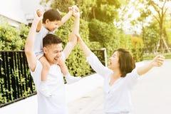 Padre asiatico sveglio che trasporta sulle spalle suo figlio con la sua moglie nel parco Famiglia emozionante che solleva le mani immagine stock