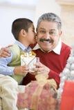 Padre asombrosamente del muchacho con el regalo de Navidad Foto de archivo