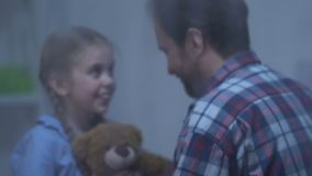 Padre atento que abraza a la niña linda, tiempo feliz del gasto de la familia junto metrajes