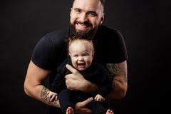 Padre atlético joven con el bebé adorable en fondo negro Fotografía de archivo