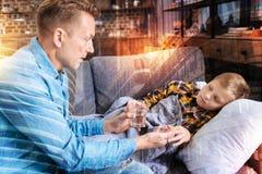 Padre attento che dà un bicchiere d'acqua e le pillole al suo bambino fotografia stock