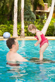 Padre attivo che insegna a sua figlia del bambino a nuotare in stagno sulla località di soggiorno tropicale Fotografie Stock