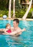 Padre attivo che insegna a sua figlia del bambino a nuotare in stagno sulla località di soggiorno tropicale Fotografia Stock Libera da Diritti