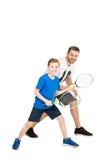 Padre attivo e figlio con le racchette di tennis isolate su bianco Fotografia Stock Libera da Diritti