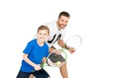 Padre attivo e figlio con le racchette di tennis isolate su bianco Fotografie Stock
