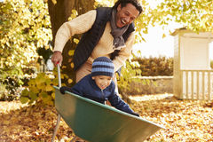 Padre In Autumn Garden Gives Son Ride in carriola fotografia stock