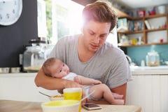 Padre With Baby Daughter que comprueba el teléfono móvil en cocina Fotos de archivo