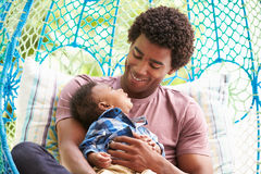 Padre With Baby Son che si rilassa sull'oscillazione all'aperto Seat del giardino Immagine Stock Libera da Diritti