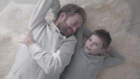 Padre barbudo de Smilling y su pequeño hijo que mienten en la alfombra blanca de la piel y tener conversación interesante Charla  almacen de video