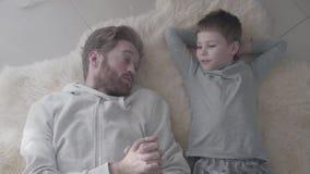 Padre barbudo y su pequeño hijo que mienten en la alfombra blanca de la piel y tener conversación interesante Padre-niño almacen de metraje de vídeo