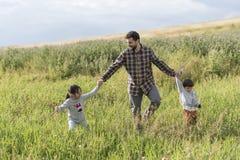 Padre barbuto che cammina con il suoi derivato e figlio nel giorno di primavera Fotografia Stock Libera da Diritti