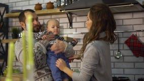 Padre barbuto in maglione caldo che gioca con il piccolo figlio del bambino che è in armi della madre nella cucina La donna dà il stock footage