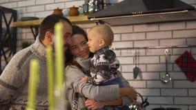 Padre barbuto in maglione caldo che gioca con il piccolo figlio del bambino che è in armi della madre nella cucina Bambino che pr video d archivio