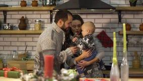 Padre barbuto in maglione caldo che gioca con il piccolo figlio del bambino in armi della madre nella cucina L'uomo dà il vaso di archivi video