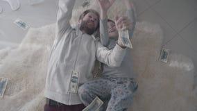 Padre bardado alegre e hijo feliz que mienten en el dinero de cogida de la alfombra blanca de la piel que cae desde arriba Papá d metrajes