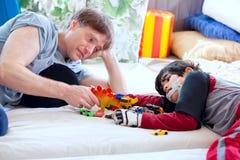 Padre bello che gioca le automobili con il figlio disabile Immagine Stock Libera da Diritti