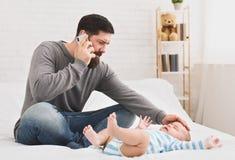 Padre cariñoso joven serio que toca su frente del bebé foto de archivo