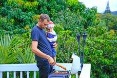 Padre cariñoso joven y su hija linda que asan a la parrilla la carne Foto de archivo libre de regalías