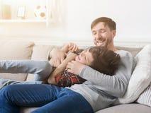 Padre cariñoso que se divierte con su hijo en el sofá imagen de archivo libre de regalías