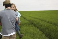 Padre Carrying Happy Daughter en campo Imagen de archivo