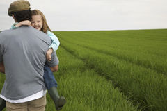Padre Carrying Happy Daughter nel campo Immagine Stock