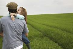 Padre Carrying Happy Daughter nel campo Fotografia Stock