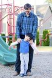 Padre che aiuta figlio invalido al campo da giuoco Immagine Stock Libera da Diritti