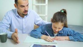 Padre che aiuta sua figlia a fare compito stock footage