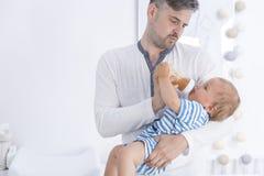 Padre che alimenta il suo bambino immagine stock libera da diritti
