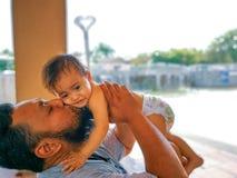 Padre che bacia bambino sulla guancia immagine stock
