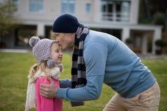 Padre che bacia sua figlia in giardino fotografia stock