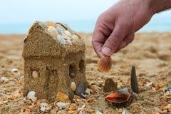 Padre che costruisce una casa della sabbia su una spiaggia Immagine Stock