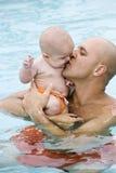 Padre che dà bacio del bambino nella piscina Fotografie Stock Libere da Diritti
