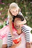 Padre che dà giro della figlia sulle spalle Fotografia Stock