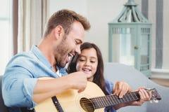 Padre che gioca chitarra con la figlia Immagine Stock