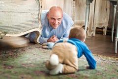Padre che gioca con il bambino sul pavimento Immagini Stock Libere da Diritti